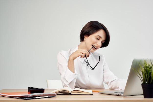 Vrouwelijke secretaresse zit aan een bureau voor een laptop in een kantoor met een wit overhemd