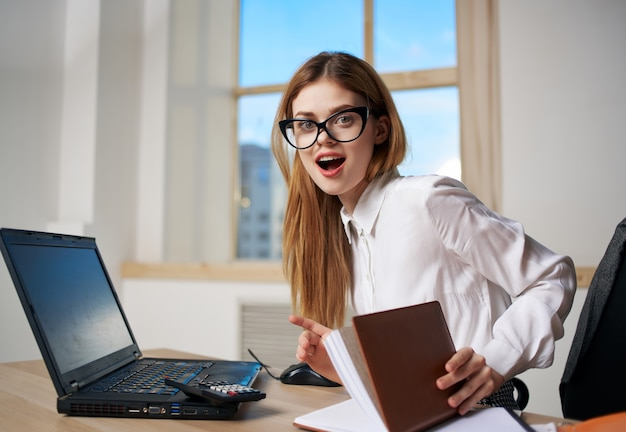 Vrouwelijke secretaresse zit aan haar bureau laptop professionals kantoor