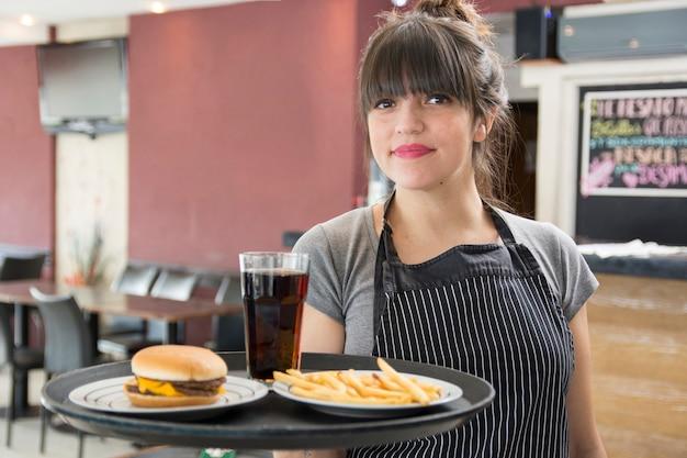 Vrouwelijke serveerster houden lade van cocktail; kip hamburger en frietjes