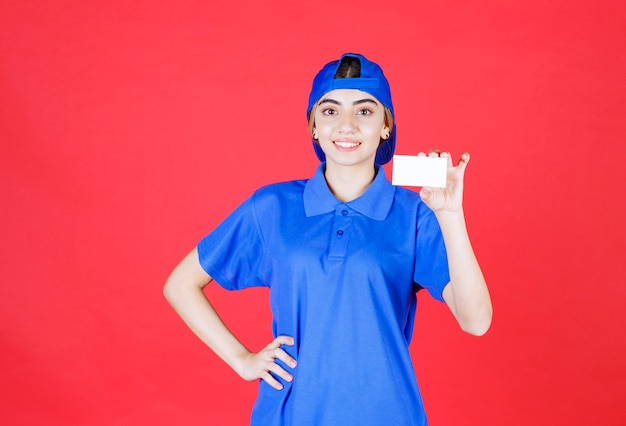 Vrouwelijke serviceagent die in blauw uniform haar visitekaartje voorstelt.