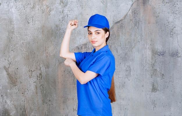 Vrouwelijke serviceagent in blauw uniform demonstreren zijn armspieren.