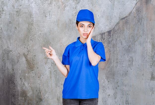 Vrouwelijke serviceagent in blauw uniform die aan de linkerkant te zien is.