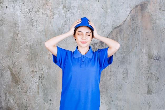 Vrouwelijke serviceagent in blauw uniform die beide handen achter haar hoofd zet.