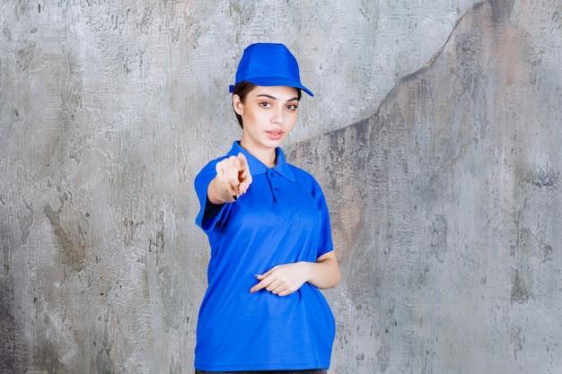 Vrouwelijke serviceagent in blauw uniform die de persoon vooruit laat zien.