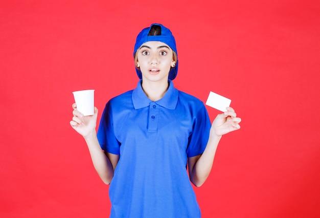 Vrouwelijke serviceagent in blauw uniform die een kopje drank vasthoudt en haar visitekaartje presenteert terwijl er verbaasd uitziet.