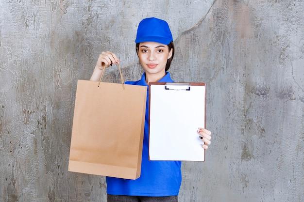 Vrouwelijke serviceagent in blauw uniform die een papieren zak vasthoudt en om een handtekening vraagt.