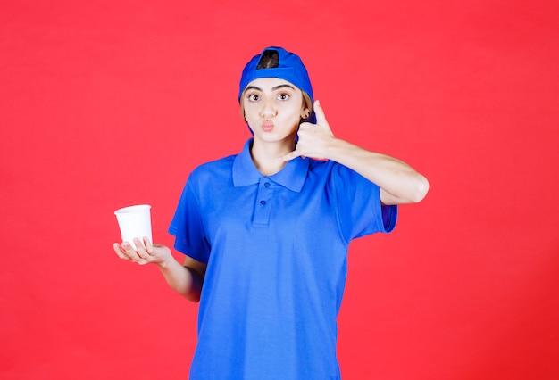 Vrouwelijke serviceagent in blauw uniform die een wegwerpbeker houdt en om een telefoontje vraagt.