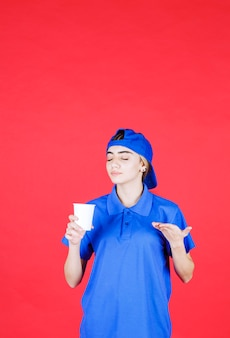 Vrouwelijke serviceagent in blauw uniform die een wegwerpbeker vasthoudt en de smaak ruikt.