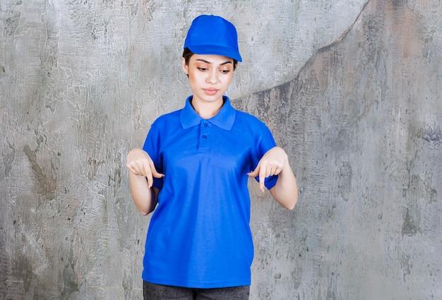 Vrouwelijke serviceagent in blauw uniform die naar beneden toont.