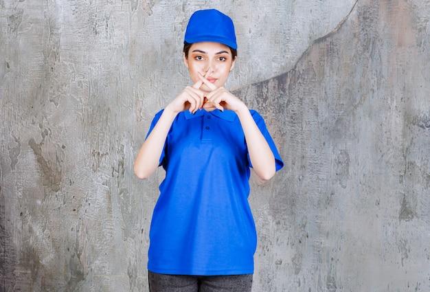 Vrouwelijke serviceagent in blauw uniform die om stilte vraagt.