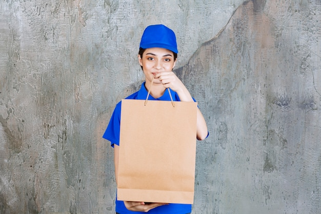 Vrouwelijke serviceagent in blauw uniform met een kartonnen boodschappentas en deze aan de klant te geven.