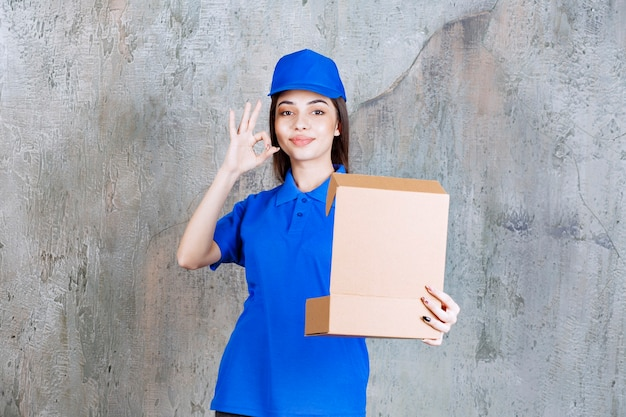 Vrouwelijke serviceagent in blauw uniform met een open kartonnen doos en een positief handteken