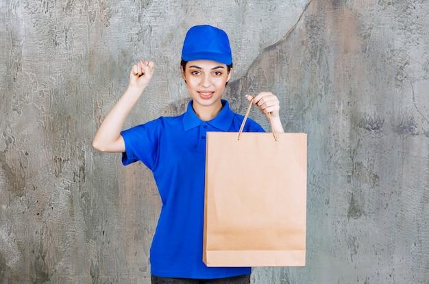 Vrouwelijke serviceagent in blauw uniform met een papieren zak en positief handteken.