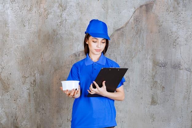 Vrouwelijke serviceagent in blauw uniform met een plastic kom en een zwarte klantenmap.