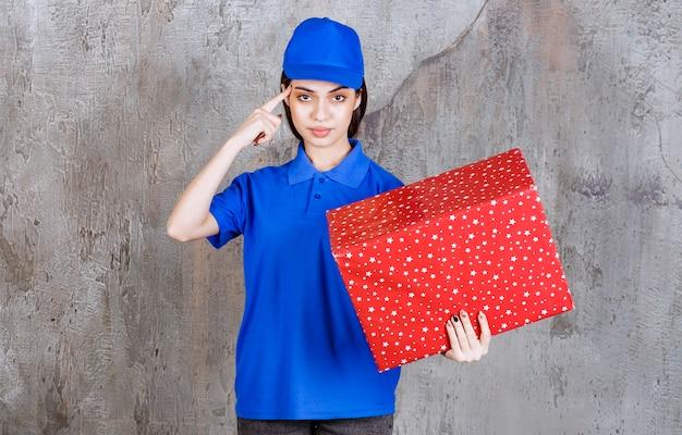 Vrouwelijke serviceagent in blauw uniform met een rode geschenkdoos met witte stippen erop en ziet er attent of dromerig uit.