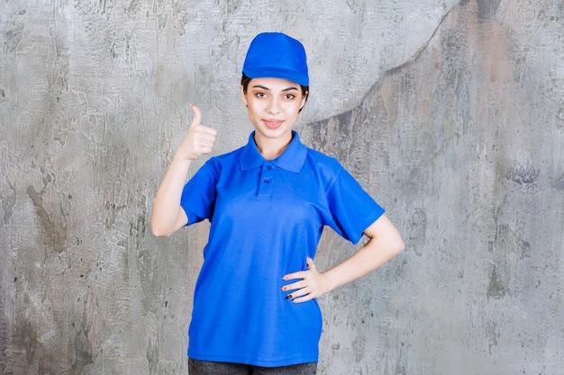Vrouwelijke serviceagent in blauw uniform met positief handteken