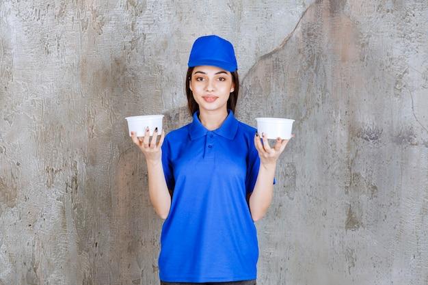 Vrouwelijke serviceagent in blauw uniform met twee plastic bekers.