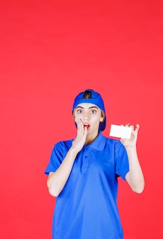 Vrouwelijke serviceagent in blauw uniform presenteert haar visitekaartje en ziet er bang uit.