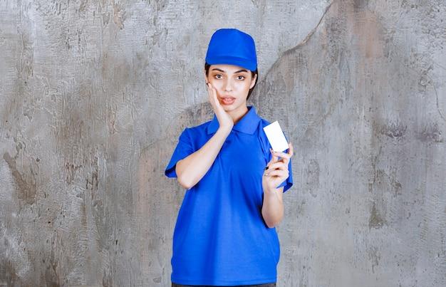 Vrouwelijke serviceagent in blauw uniform presenteert haar visitekaartje en ziet er verward of attent uit.