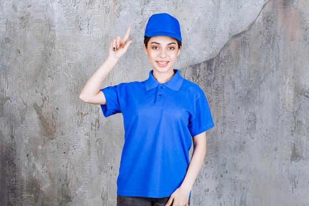 Vrouwelijke serviceagent in blauw uniform wijst naar boven.