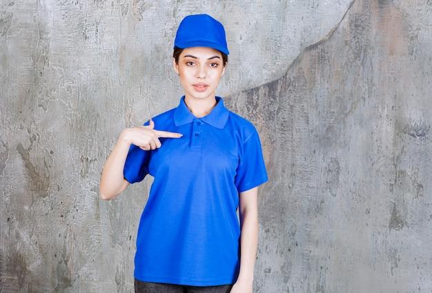 Vrouwelijke serviceagent in blauw uniform wijzend op zichzelf.