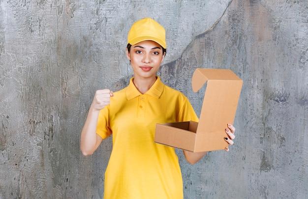 Vrouwelijke serviceagent in geel uniform die een open kartonnen doos houdt en een positief handteken toont.