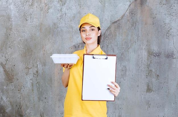 Vrouwelijke serviceagent in geel uniform die een plastic afhaaldoos vasthoudt en om een handtekening vraagt.