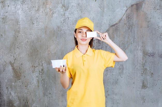 Vrouwelijke serviceagent in geel uniform die een plastic meeneemkom vasthoudt en haar visitekaartje voorstelt.