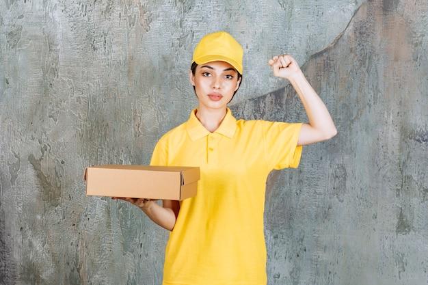 Vrouwelijke serviceagent in geel uniform met een kartonnen doos en positief handteken tonen.