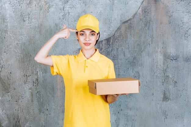 Vrouwelijke serviceagent in geel uniform met een kartonnen doos en ziet er verward en attent uit.
