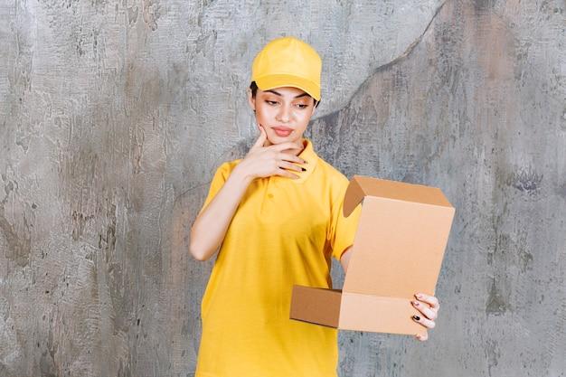 Vrouwelijke serviceagent in geel uniform met een open kartonnen doos en ziet er verward en attent uit