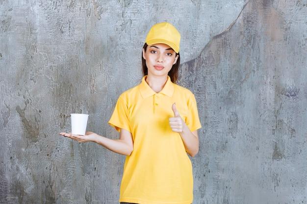 Vrouwelijke serviceagent in geel uniform met een plastic beker en positief handteken.