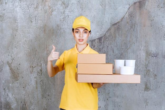Vrouwelijke serviceagent in geel uniform met een voorraad afhaalkartonnen dozen en plastic bekers terwijl ze een positief handteken toont