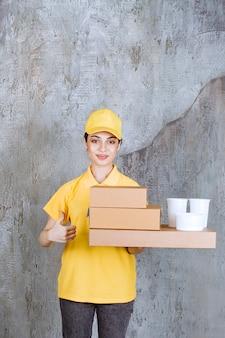 Vrouwelijke serviceagent in geel uniform met een voorraad afhaalmaaltijden kartonnen dozen en plastic bekers.