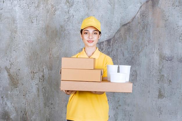 Vrouwelijke serviceagent in geel uniform met een voorraad meeneemkartonnen dozen en plastic bekers.