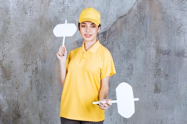 Vrouwelijke serviceagent in geel uniform met infobureaus in beide handen.