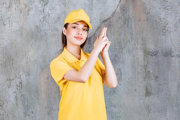 Vrouwelijke serviceagent in geel uniform staande op betonnen muur en handpistoolteken vasthoudend.