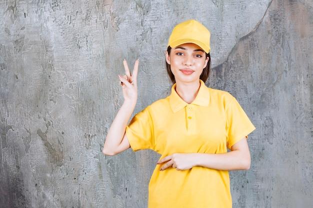 Vrouwelijke serviceagent in geel uniform staande op betonnen muur en vrede te sturen.