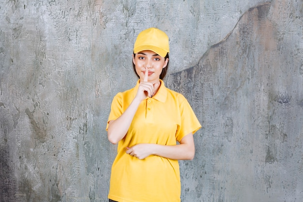 Vrouwelijke serviceagent in geel uniform staat op betonnen muur en vraagt om stilte.