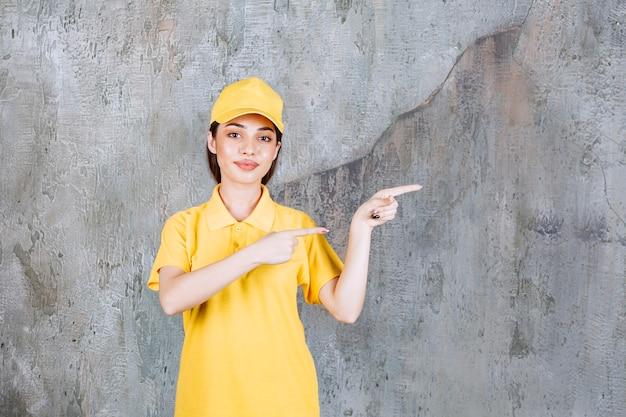 Vrouwelijke serviceagent in geel uniform staat op betonnen muur en wijst naar de rechterkant.
