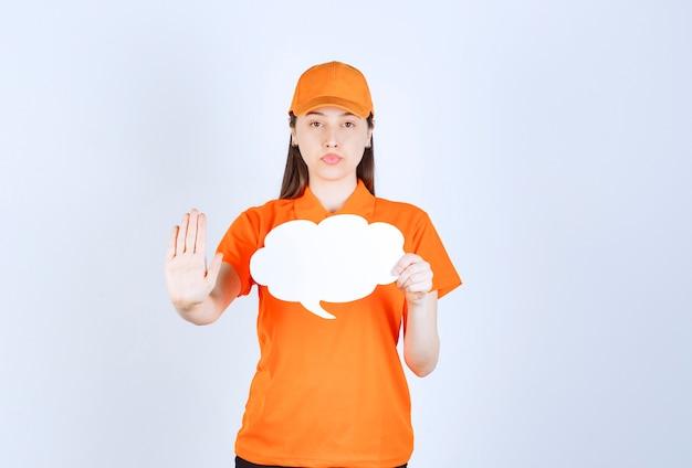Vrouwelijke serviceagent in oranje kleur dresscode met een infobord in de vorm van een wolk en iets stoppen.