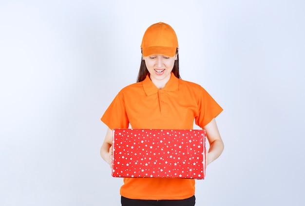 Vrouwelijke serviceagent in oranje kleur dresscode met een rode geschenkdoos.