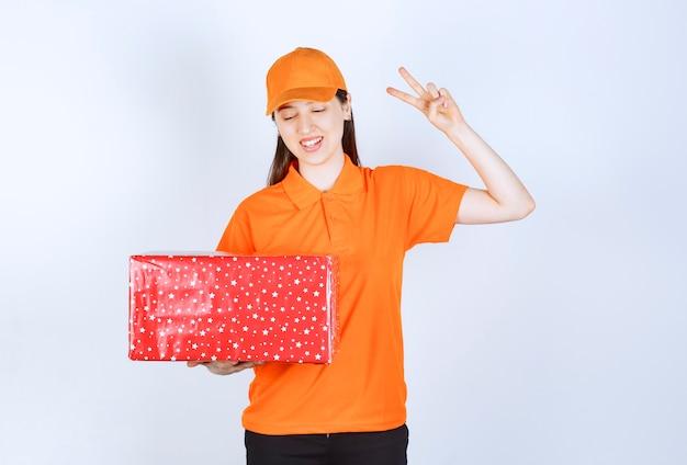 Vrouwelijke serviceagent in oranje kleur uniform met een rode geschenkdoos en vredesteken tonen.