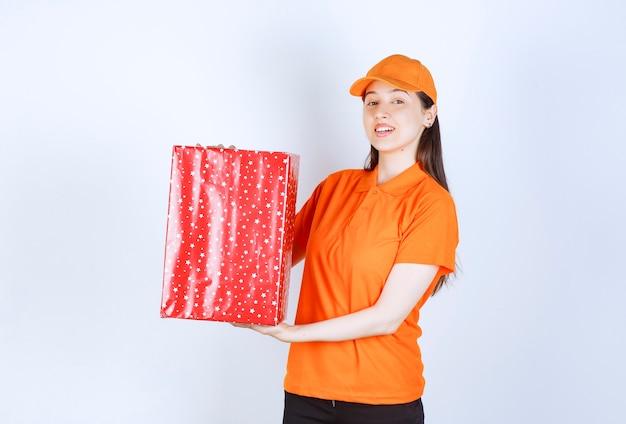 Vrouwelijke serviceagent in oranje kleur uniform met een rode geschenkdoos.