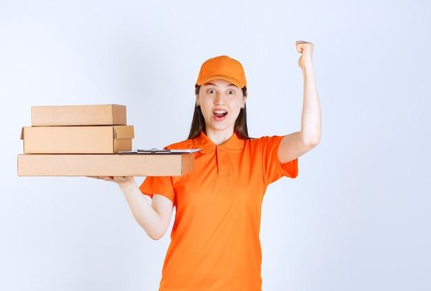 Vrouwelijke serviceagent in oranje kleuruniform die meerdere kartonnen dozen levert en een positief handteken toont.
