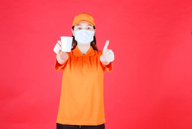 Vrouwelijke serviceagent in oranje kleuruniform en masker die een wegwerpbeker vasthoudt en positief handteken toont.