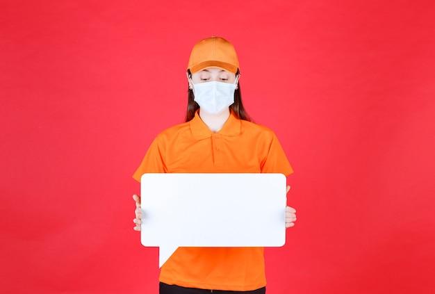 Vrouwelijke serviceagent in oranje kleuruniform en masker met een wit rechthoekig infobord.