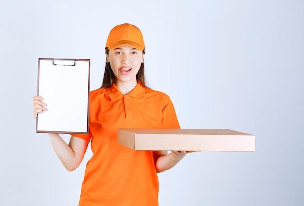 Vrouwelijke serviceagent in oranje kleuruniform met een kartonnen pizzadoos voor afhaalmaaltijden en vraagt om handtekening.
