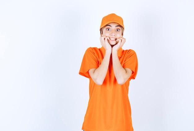 Vrouwelijke serviceagent in oranje uniform bedekt haar mond en ziet er bang uit