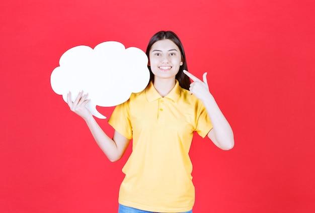 Vrouwelijke servicemedewerker die een infobalie in de vorm van een wolk vasthoudt en zich positief voelt
